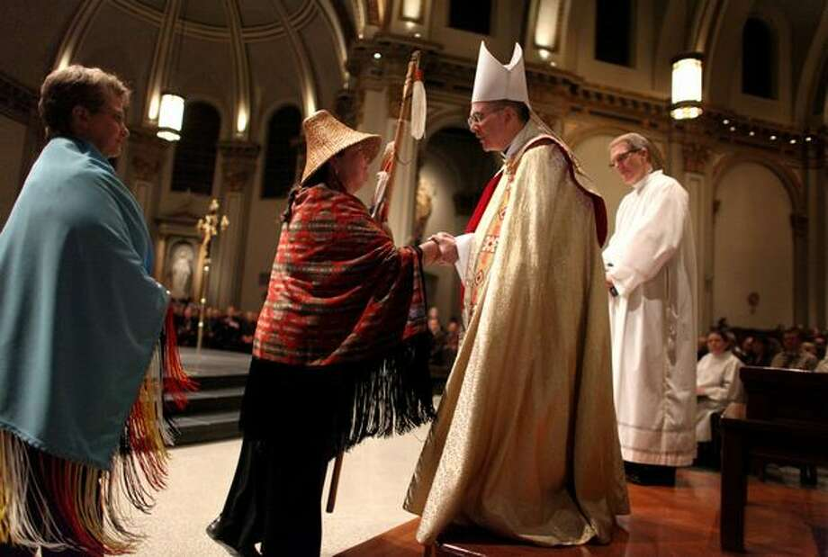 Archbishop J. Peter Sartain is welcomed to the Pacific Northwest by Kay Knott of the Upper Skagit Tribe during a Rite of Reception ceremony at Saint James Cathedral. Sartain succeeded Archbishop Alex Brunett as leader of the Archdiocese of Seattle. Photo: Joshua Trujillo, Seattlepi.com