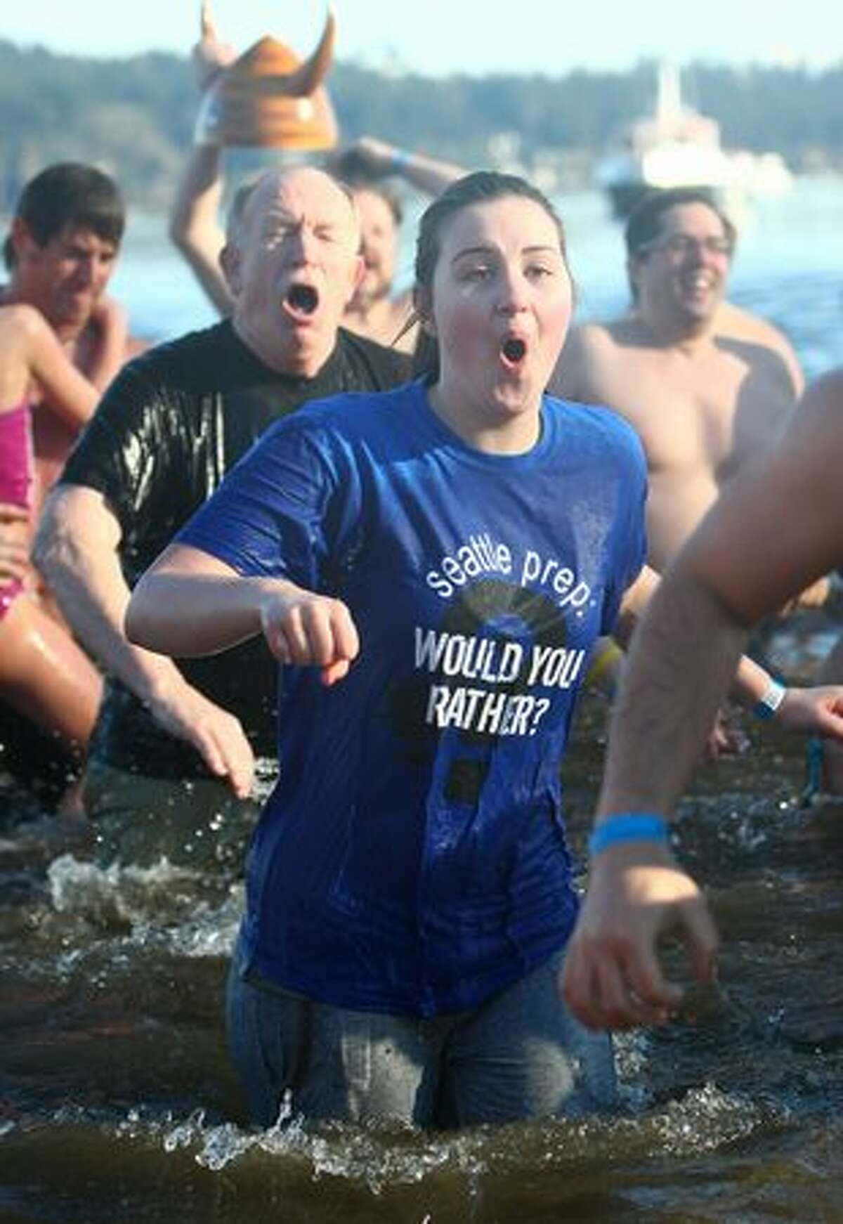 People react to the cold water during the annual Polar Bear Plunge at Matthews Beach on Lake Washington Saturday.