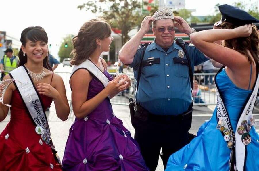 A Seattle Police officer trades his hat for a tiara before Seattle's annual Torchlight Parade.