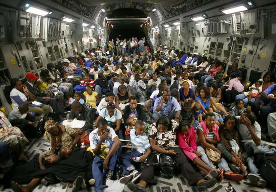 Nearly 200 evacuees are strapped to the floor of a C-17 Globemaster III at the Port-Au-Prince airport. The aircraft and its crew from McChord Air Force Base participated in a massive airlift of personnel and relief supplies into earthquake-damaged Haiti. Evacuees were taken from Port-Au-Prince to Orlando, Florida. Photo: Joshua Trujillo, Seattlepi.com