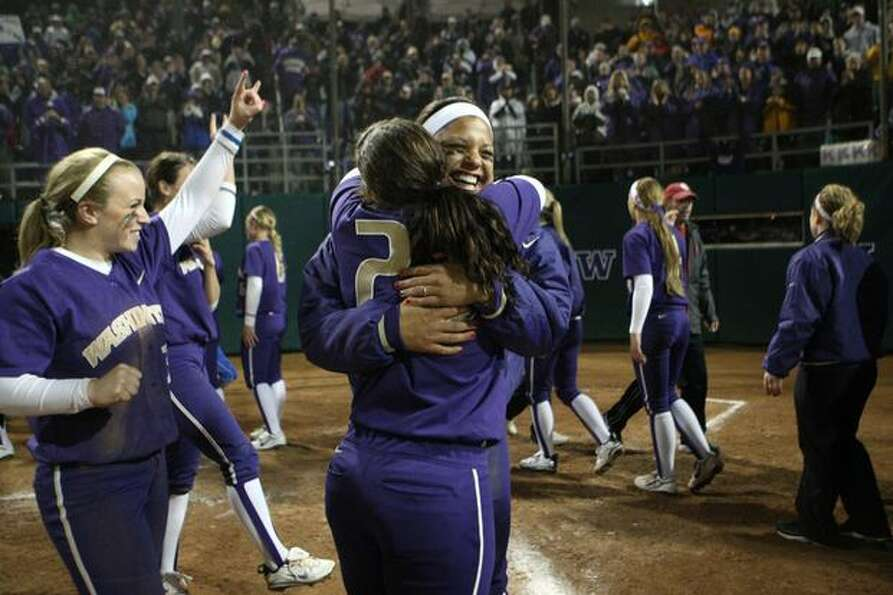 University of Washington players Baily Harris (20) and Niki Williams embrace after defeating the Uni