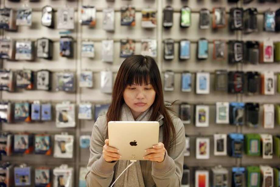 Winnie Chan of Vancouver, B.C. tries out Apple's iPad during the release of the much-hyped device at the University Village Apple Store. Chan drove with friends from Vancouver to purchase the iPad. Hundreds of people waited, some as long as 15 hours, to have one of the devices. Photo: Joshua Trujillo, Seattlepi.com