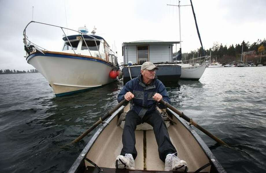 Ted Stoughton rows his skiff away from his floating home on Bainbridge Island's Eagle Harbor. Stoughton, along with other boat owners and the liveaboard community were served eviction notices by the Washington State Department of Natural Resources after plans with the Bainbridge City Council for an open-water marina were scrapped. For decades the harbor has hosted the community made up of an assortment of boats and house barges. The floating homes were moored on the state-managed sea floor free of charge. Stoughton has lived there since 1984. The state later allowed an extension for those living on the water to stay in their homes. Photo: Joshua Trujillo, Seattlepi.com
