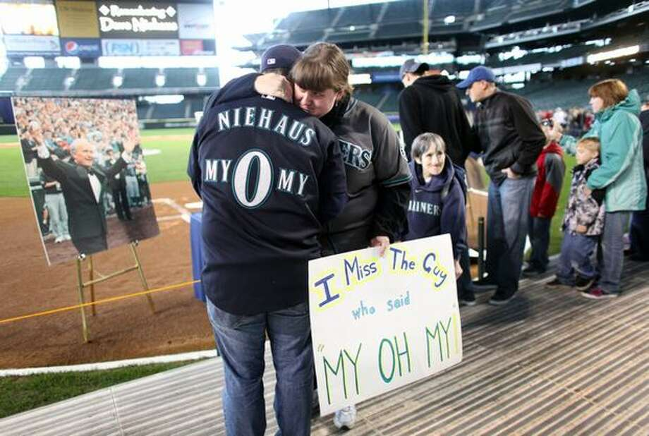 Colleen Doser embraces her boyfriend Noel Renggli during a tribute for Dave Niehaus on at Safeco Field in Seattle. Niehuas died earlier in the week from a heart attack. The popular play-by-play announcer was the voice of the Seattle Mariners since the team's inaugural season in 1977. Photo: Joshua Trujillo, Seattlepi.com