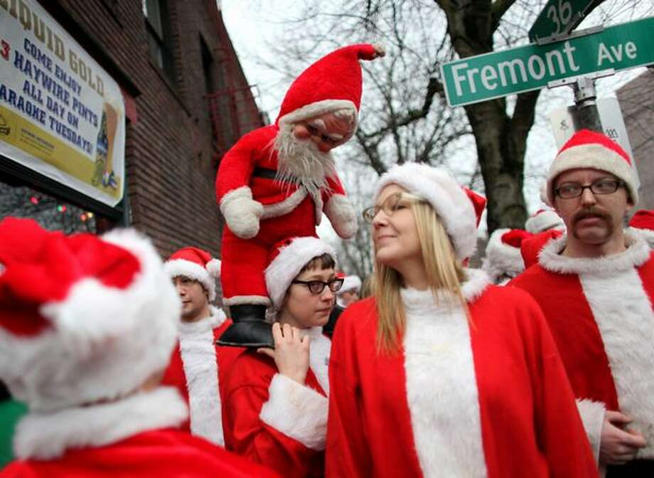 Revelers dressed as Santa Claus gather on Fremont Avenue North near some of Fremont's watering holes during SantaCon. Hundreds of jolly old elves walked the streets of Fremont, gathered in bars and consumed pitchers of Christmas cheer during the annual event. Photo: Joshua Trujillo, Seattlepi.com