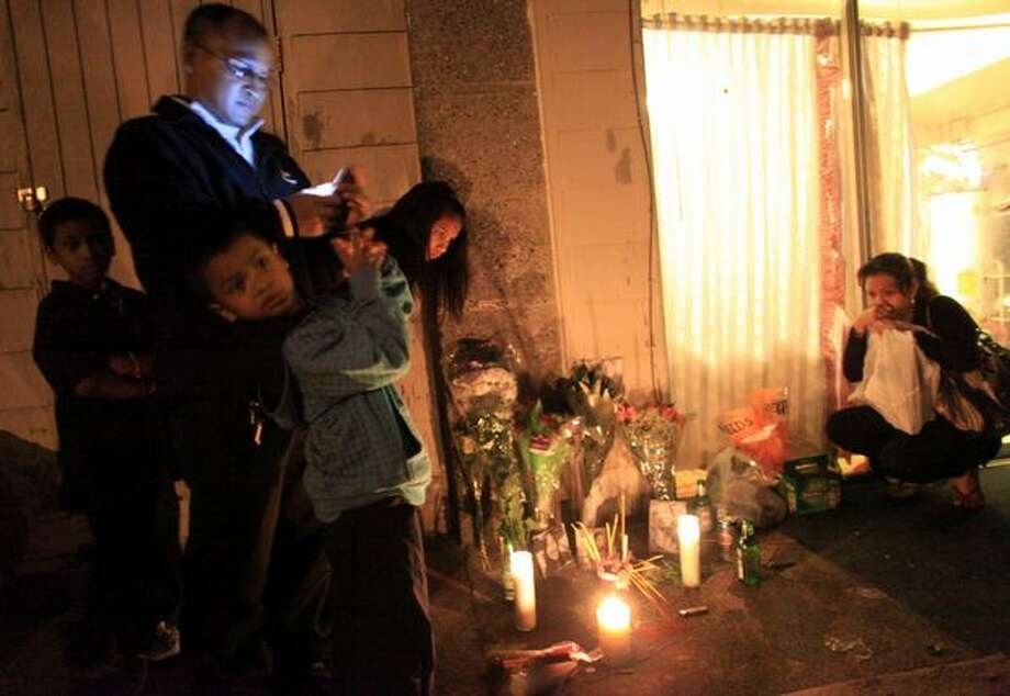 Family members gather outside a West Seattle home to light candles and visit the house where four members of the family were shot and killed Thursday. Saroeun Phan, 60, killed her two granddaughters and son-in-law Friday before turning a gun on herself. She also shot her daughter four times. The daughter survived the rampage. Photo: Joshua Trujillo, Seattlepi.com