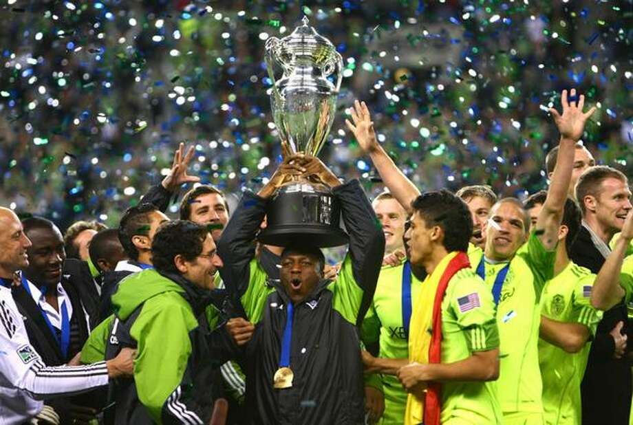 Seattle Sounders player Sanna Nyassi hoists the U.S. Open Cup trophy while surrounded by teammates after defeating Columbus Crew at Qwest Field in Seattle. Seattle defeated Columbus 2-1 to secure its second Open Cup trophy. Photo: Joshua Trujillo, Seattlepi.com