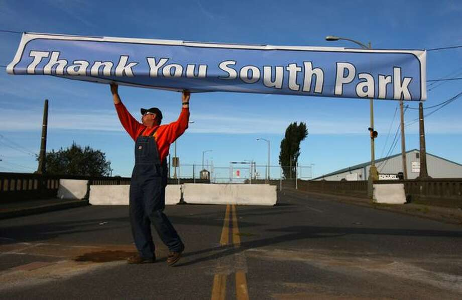 Tom Wolfe with King County's Department of Transportation hangs a banner over the South Park Bridge's closed West end after funding for a replacement was announced. Photo: Joshua Trujillo, Seattlepi.com