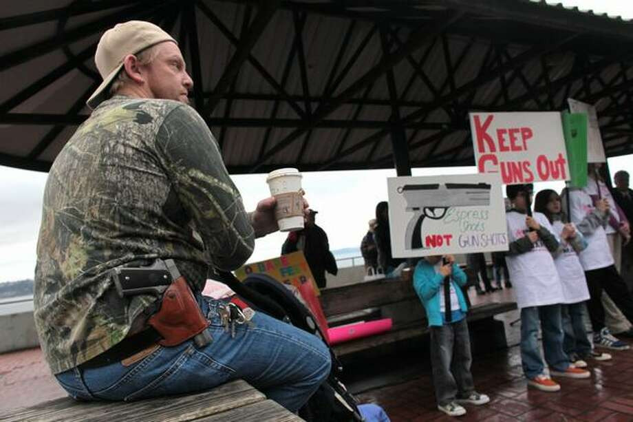 Greg Dement of Kent shows his opposition as he wears a Colt 1911 during a press event organized by Washington CeaseFire, The Brady Campaign to Prevent Gun Violence, and Washington State Million Mom March. Organizers of the event hoped to pressure Starbucks into adopting a no guns policy in all its stores. Photo: Joshua Trujillo, Seattlepi.com