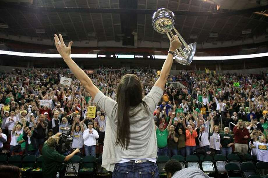 Seattle Storm player Sue Bird hoists the WNBA trophy in front of fans as the WNBA National Championship team is welcomed back to KeyArena. The Storm won their second national championship in 2010. Photo: Joshua Trujillo, Seattlepi.com