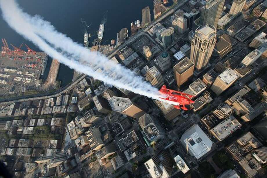 Team Oracle pilot Sean Tucker performs a practice run over downtown Seattle during Seafair week. Photo: Joshua Trujillo, Seattlepi.com