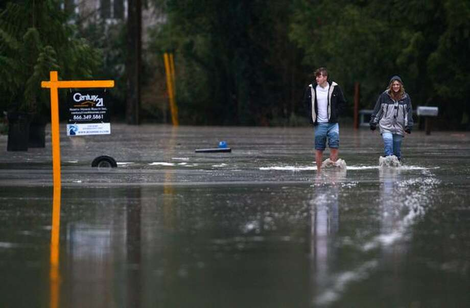 Isaiah Morris and his sister Chelsea Morris walk in their flooded neighborhood in Granite Falls. Near record rainfall caused many local rivers to rise above flood stage. About 240 homes in the area were issued a voluntary evacuation. Photo: Joshua Trujillo, Seattlepi.com