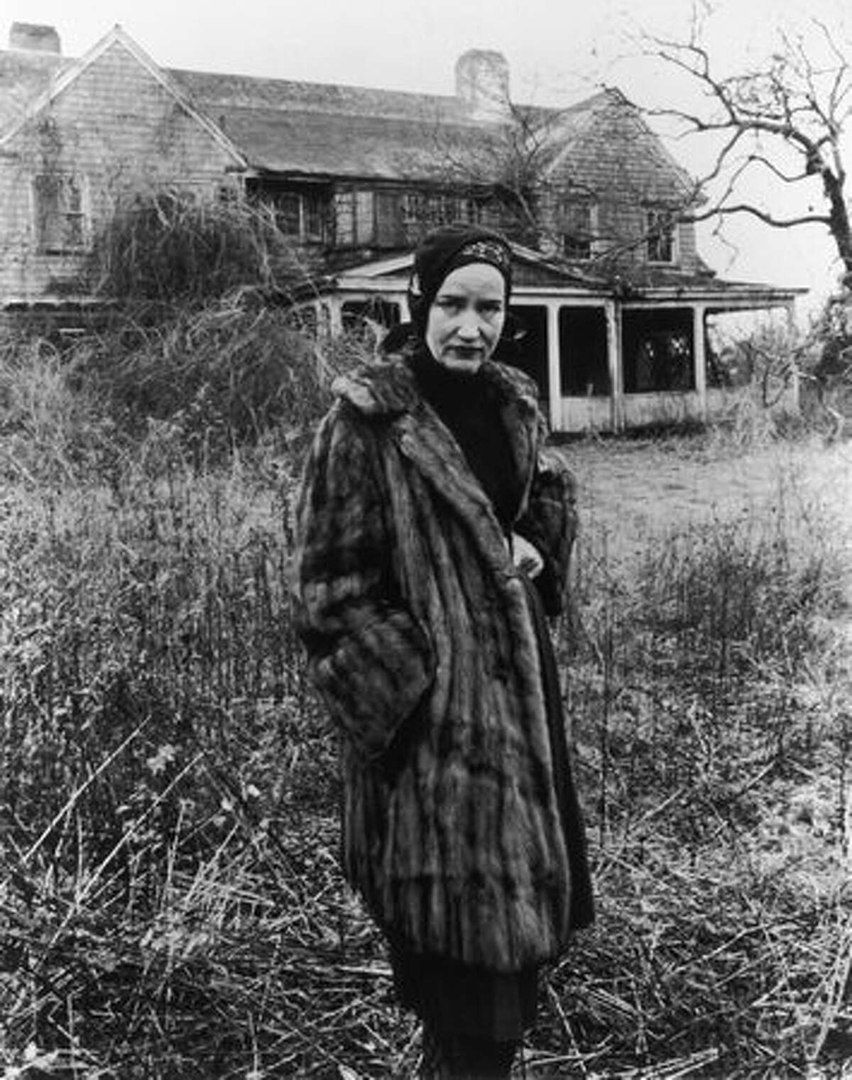 American socialite Edith Beale Jr. (1917 - 2002) wears a fur coat in front of her dilapidated Long Island mansion in a still from the 1975 documentary