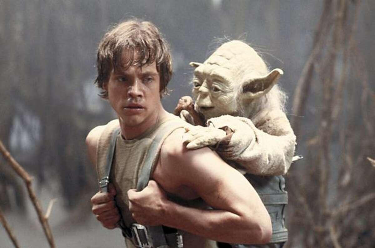 Mark Hamill as Luke Skywalker gives a piggyback ride to Yoda in