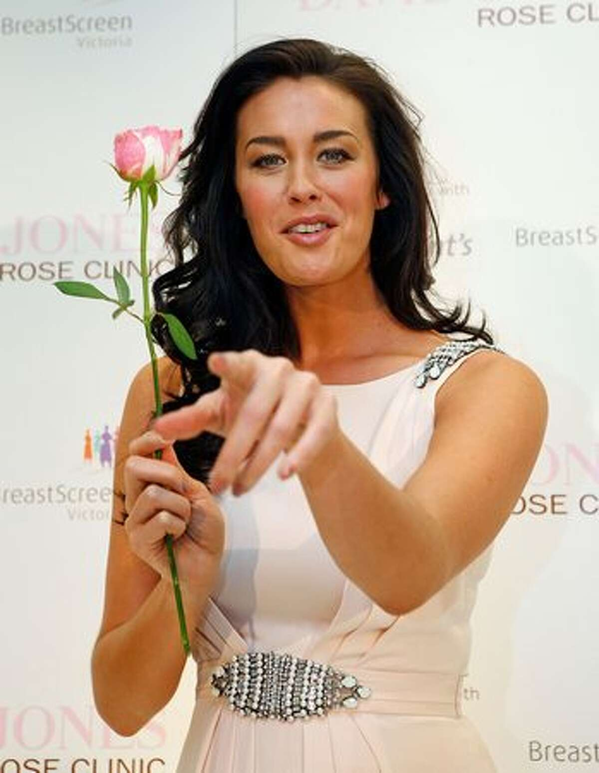 Model Megan Gale gestures while holding a rose during the announcement of a new women's health initiative at David Jones Bourke Street Mall on June 8, 2010 in Melbourne, Australia.