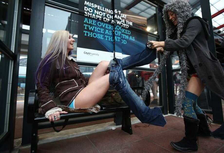 "Jane Merkutova has her pants removed by her friend Ciara Sampaio during Seattle's second ""No-Pants Light Rail Ride"" on Sunday, Jan. 9, 2011. During the event hundreds of train passengers took off their pants, surprising other riders and bystanders. The event took place in other cities around the globe on Sunday. Photo: Joshua Trujillo, Seattlepi.com"