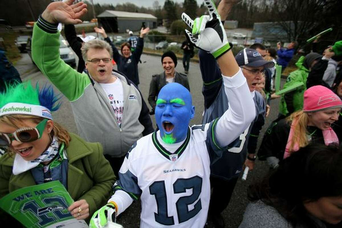 Fans, including Donny Dang, center, cheer as team busses drive past during a fan sendoff for the Seattle Seahawks near the Virginia Mason Athletic Facility in Renton.