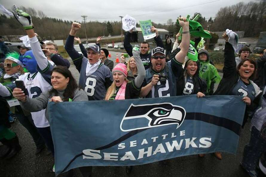 Fans cheer as team busses drive past during a fan sendoff for the Seattle Seahawks.