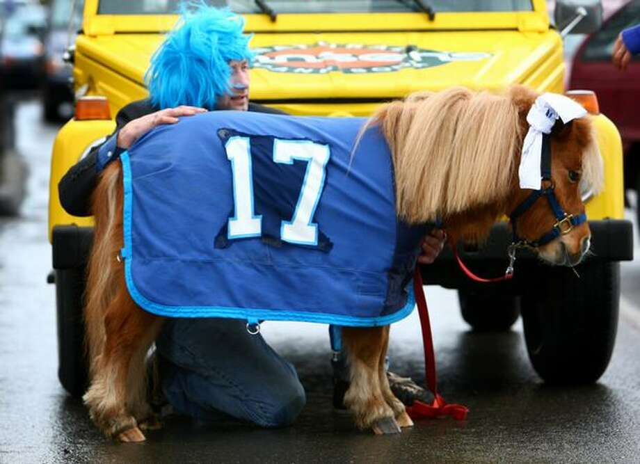 J.R. Sundholm of Snohomish sits next to his mini horse Teddy during a fan sendoff for the Seattle Seahawks on Friday near the Virginia Mason Athletic Facility in Renton. Photo: Joshua Trujillo, Seattlepi.com