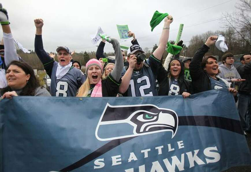 Fans cheer as team busses drive past during a fan sendoff for the Seattle Seahawks near the Virginia