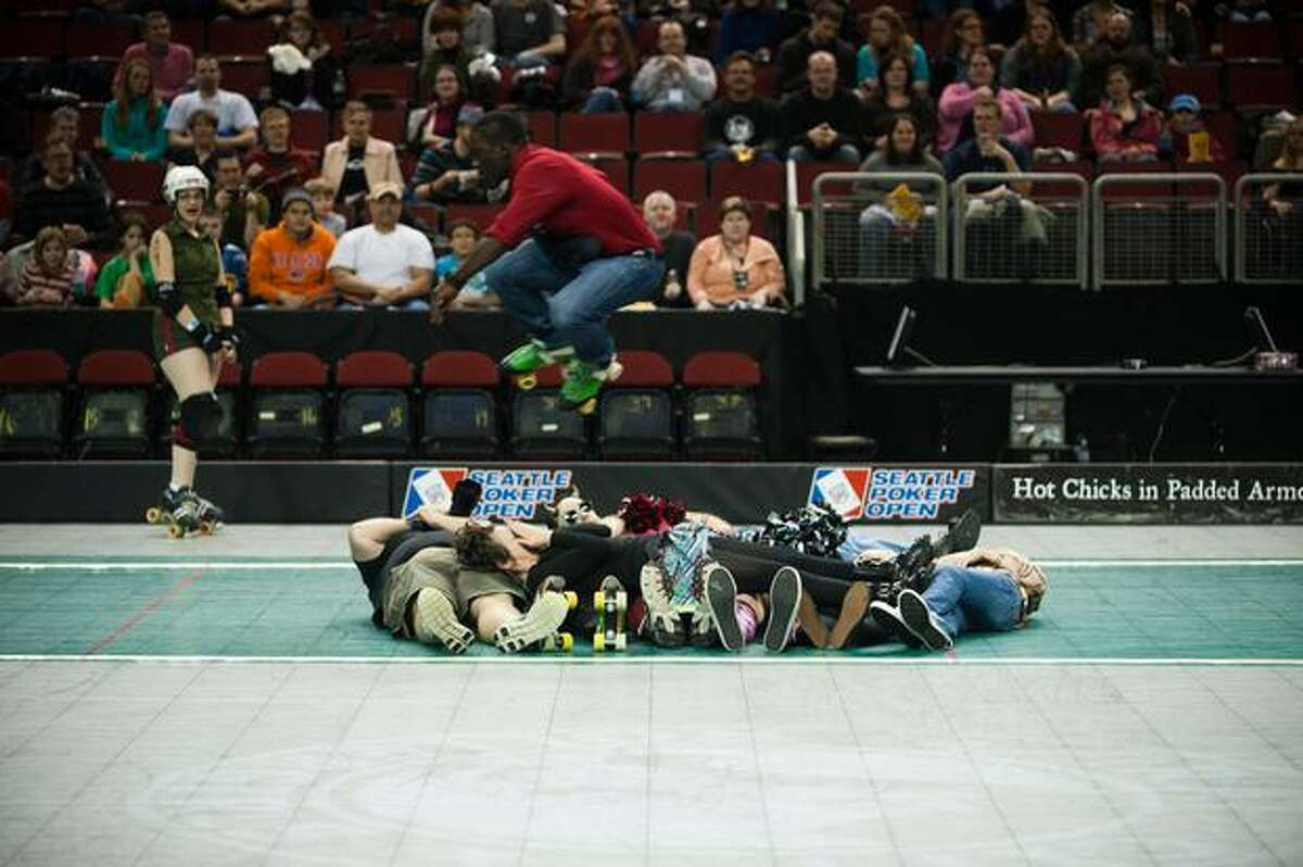 A man on roller skates jumps over seven people before the competition begins.
