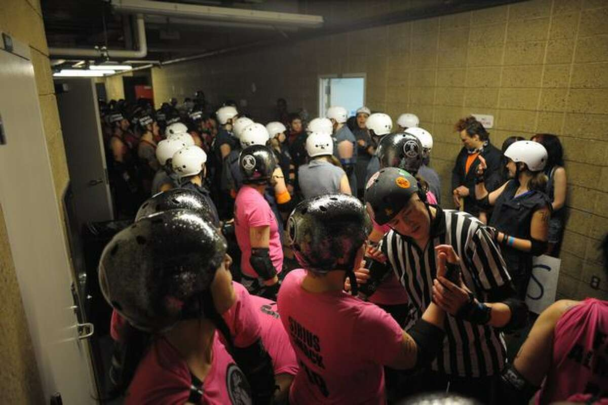 Wristguards are checked by referees before the bout begins.