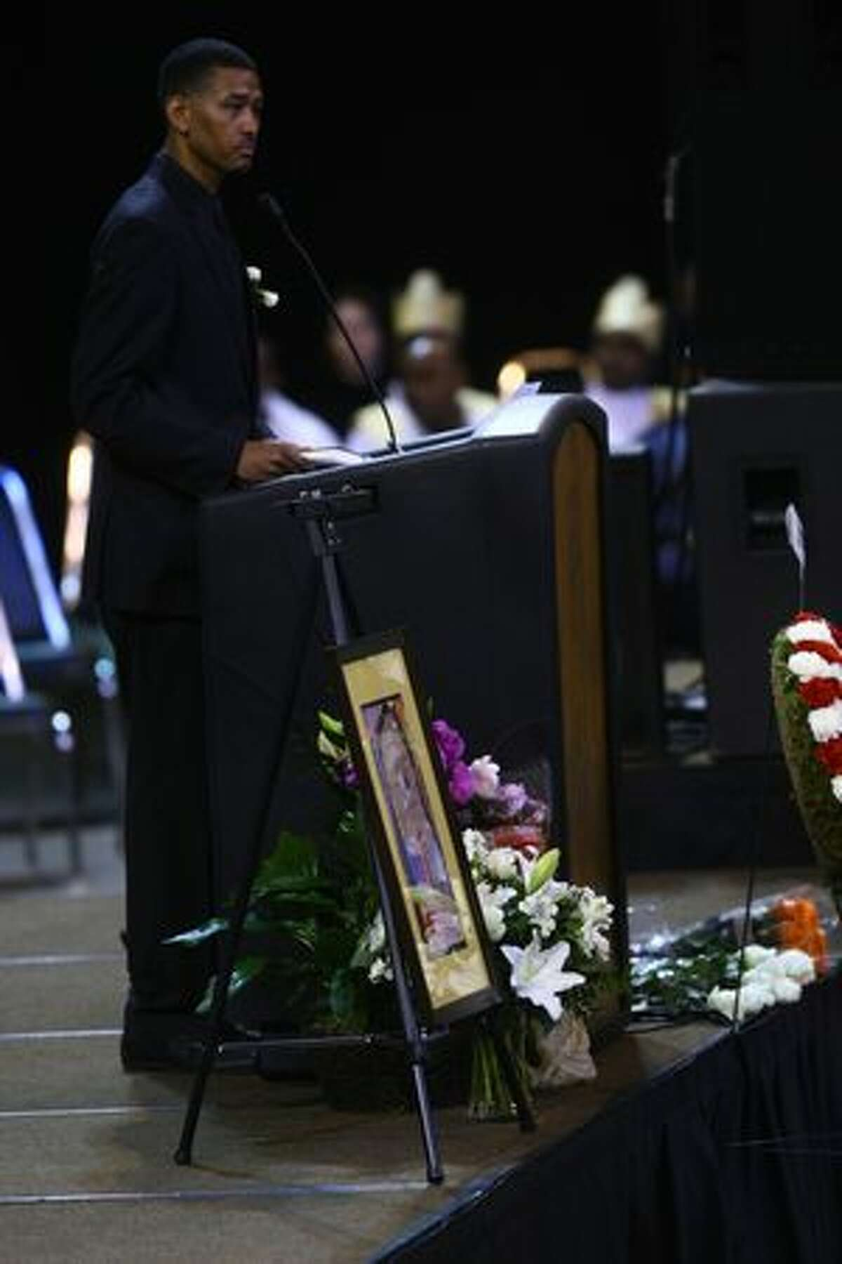 Daniel Gebregiorgis, uncle of the victims, speaks during the funeral service at KeyArena Friday.
