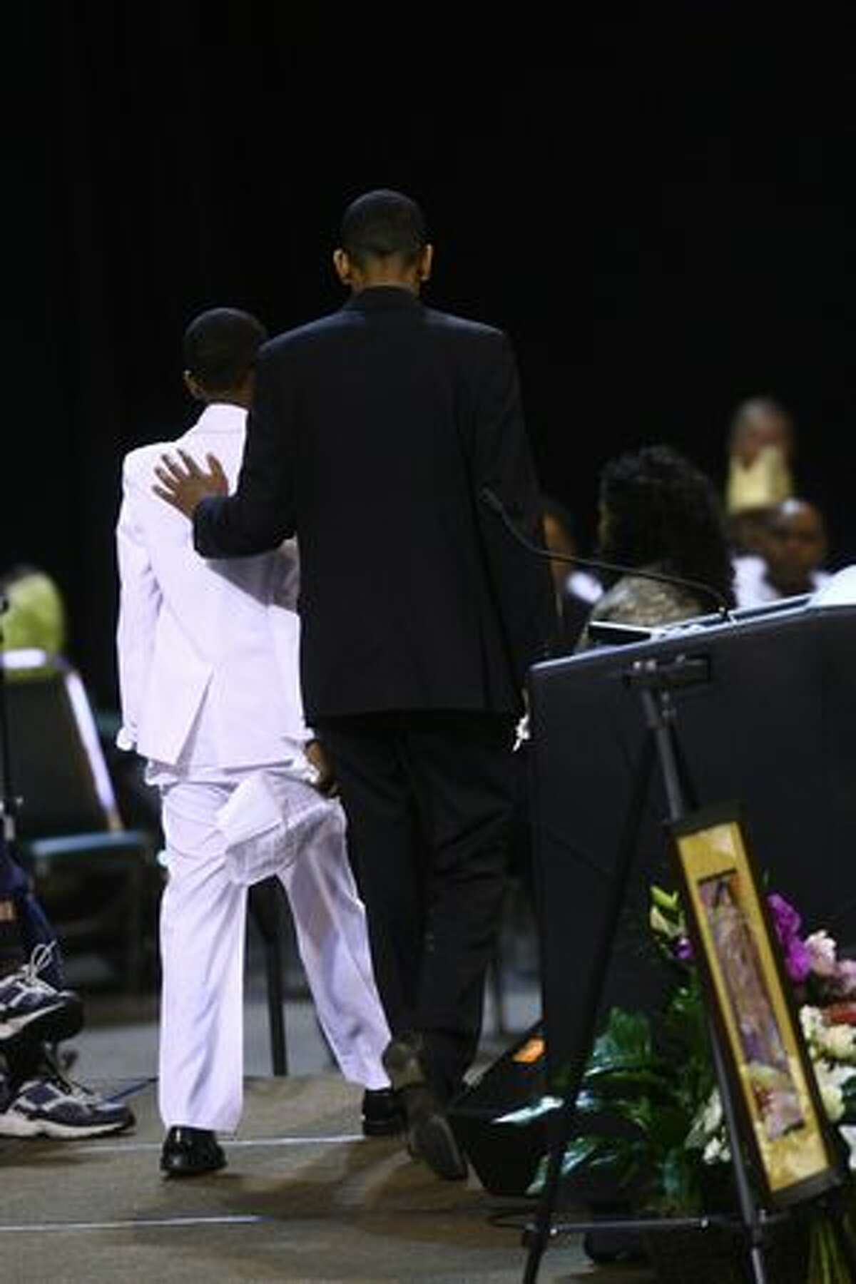 Immediate family members exit the stage after speaking about their lost family members during a funeral service at KeyArena Friday.