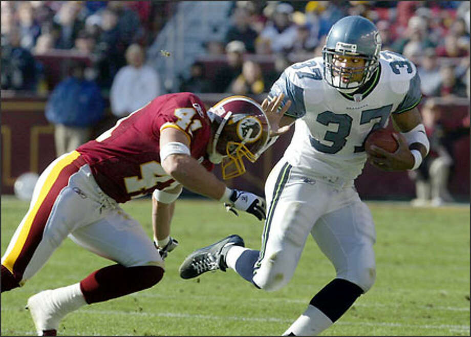 Seahawks running back Shaun Alexander (37) stiff-arms Redskins safety Matt Bowen on the Seahawks' second touchdown drive in the first quarter. Photo: Scott Eklund, Seattle Post-Intelligencer