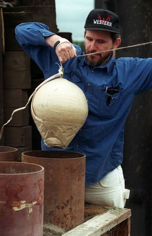 Don Guyot loads a 12-inch shell into a mortar tube in preparation for the Fourth of Jul-Ivar's Fireworks display over Elliot Bay, 1998. Photo: P-I File