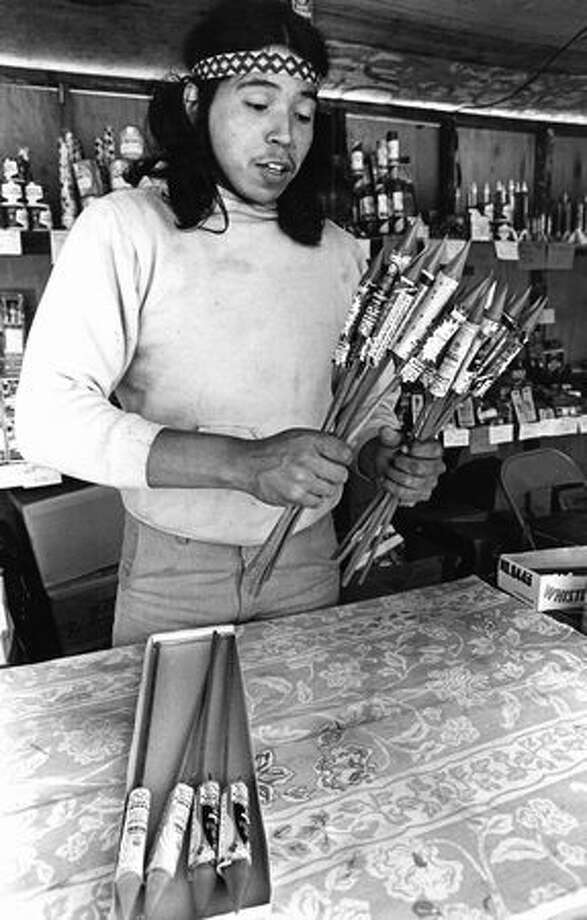 Kelly Lozier holds some fireworks while behind the counter of his fireworks stand on July 1, 1981. Lozier's stand was at the Muckleshoot Indian Reservation. Photo: P-I File