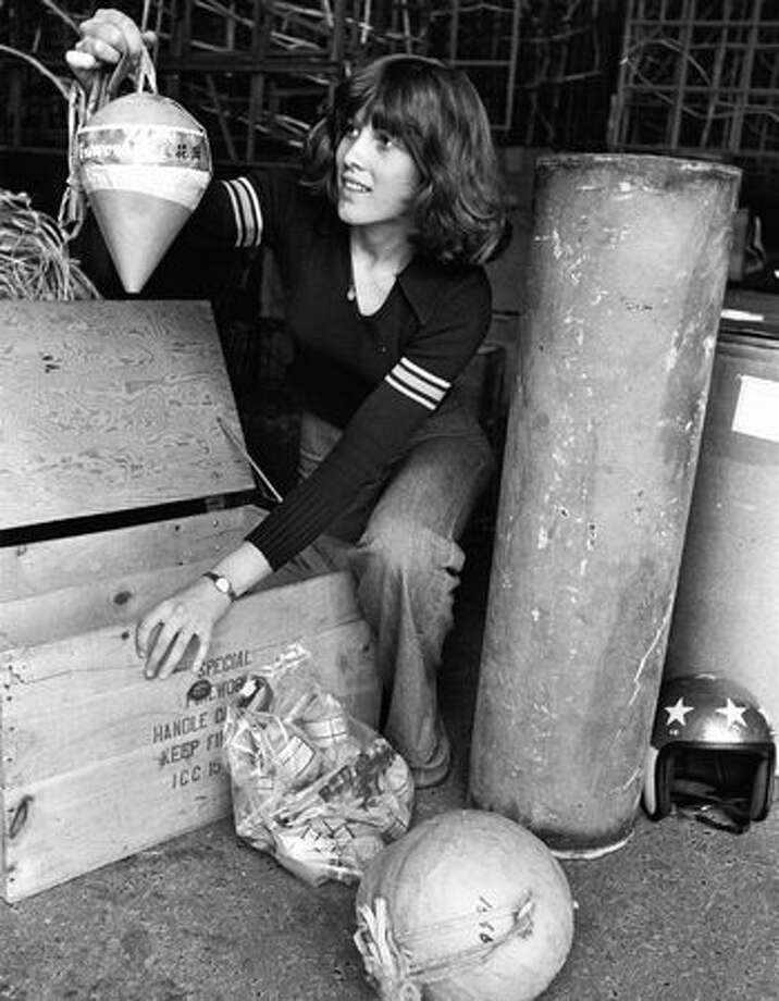 Sue Yager, pyrotechnician at Red Devil Fireworks Co., displays shells used at a Ivar's fireworks show on July 4, 1976. Photo: P-I File