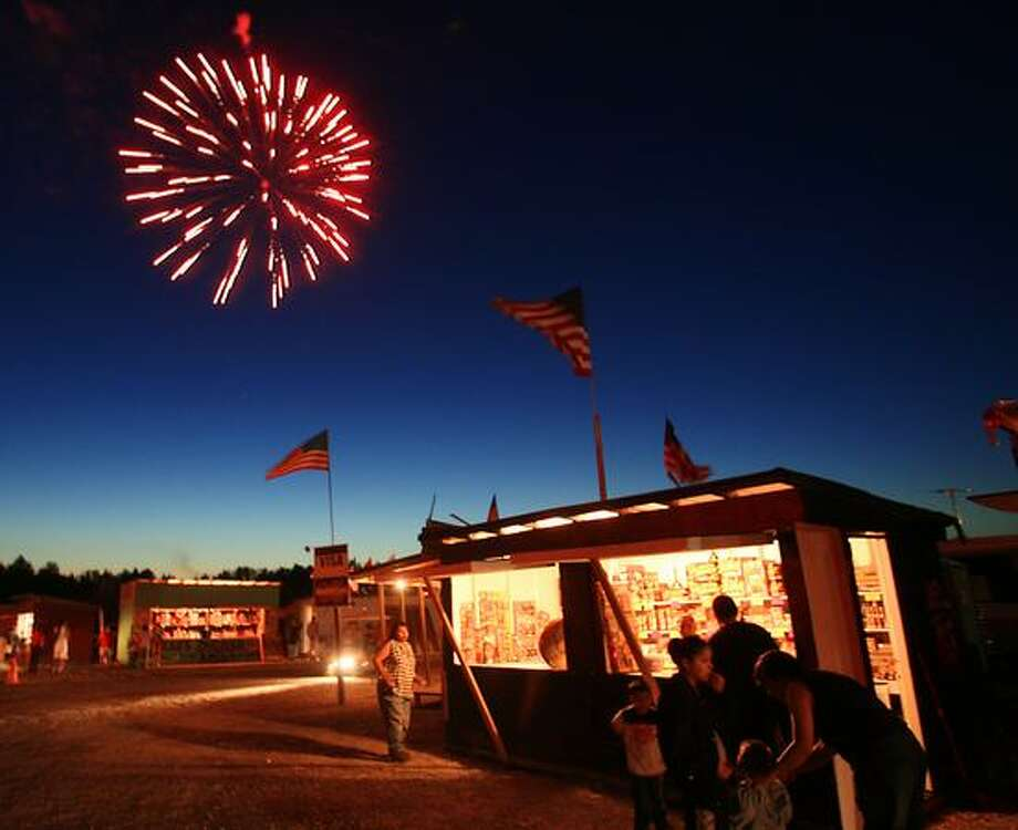 Fireworks are shot off in the background as fireworks stands are open for business at the Muckleshoot Indian Reservation in Auburn, June 2008. Photo: P-I File