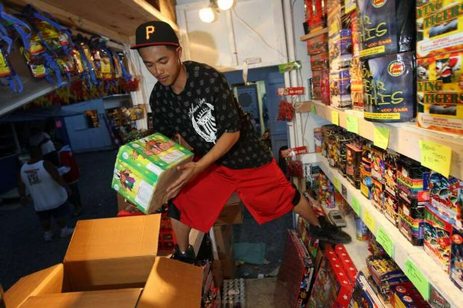 Yuttana Sou helps his brother load shelves at a Boom City stand, June 2008. Photo: P-I File