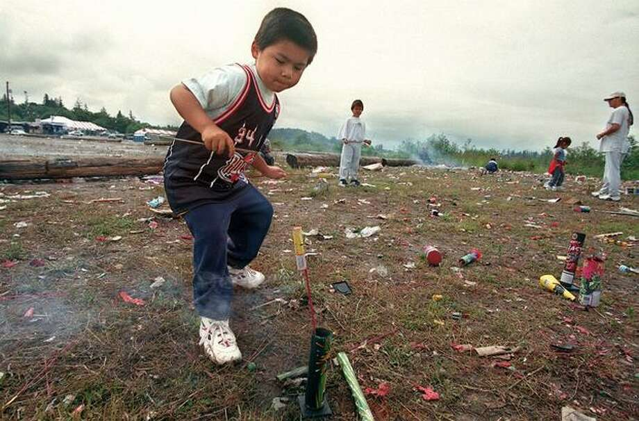 A youngster backpedals away after lighting a firecracker at Boom City in 1998. Photo: P-I File