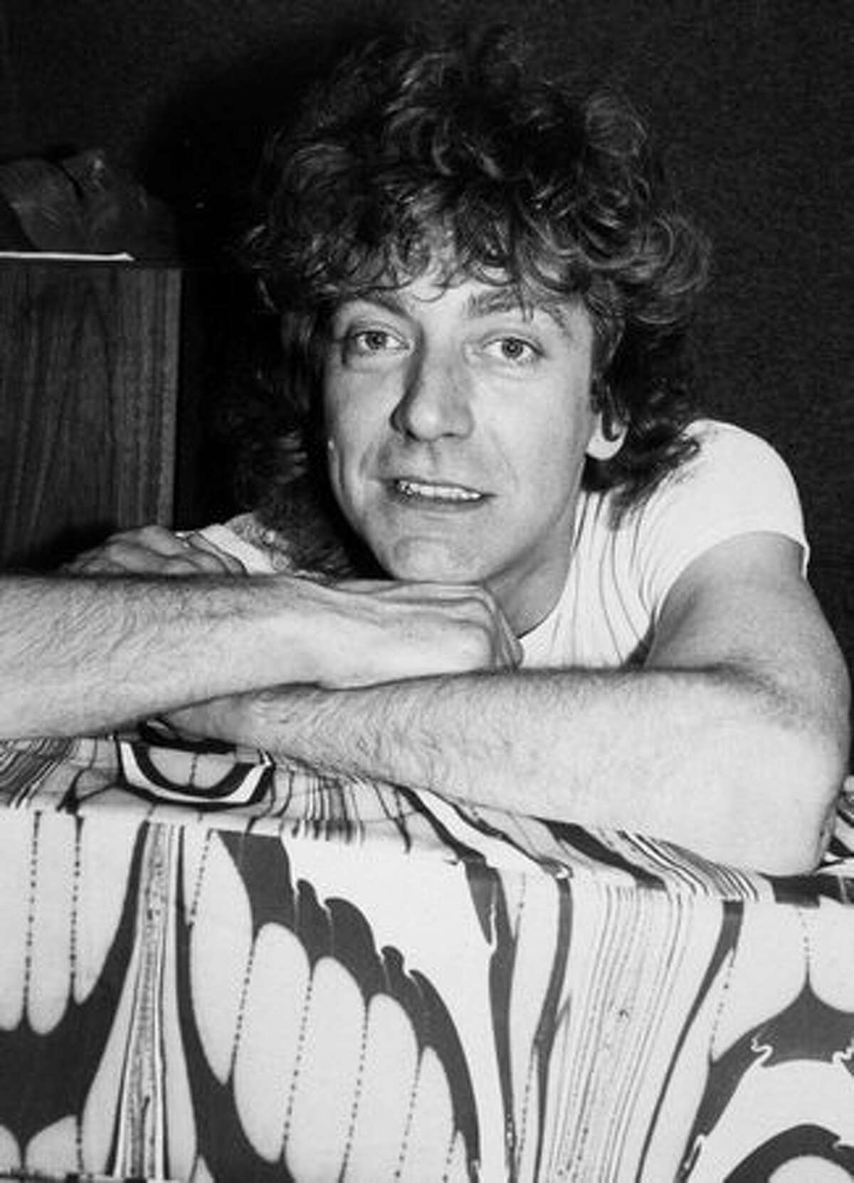 British rock singer Robert Plant poses leaning on the back of a sofa, 1982.