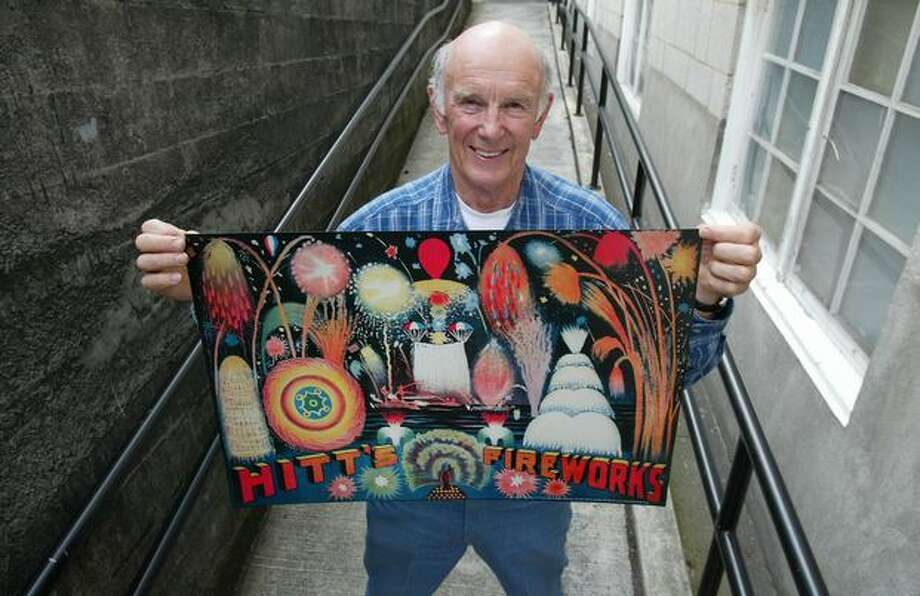 Buzz Anderson, president of Rainier Valley Historical Society in 2005, holds a reprodution of a poster for Hitt Fireworks, which produced fireworks in Seattle from 1905 to 1976. Photo: P-I File