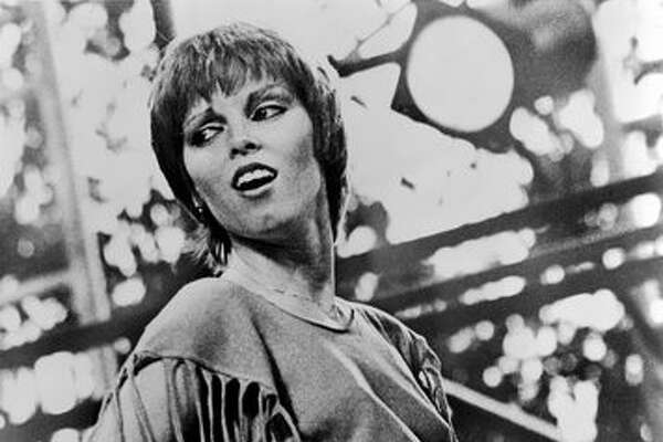 American rock and pop singer Pat Benatar glances over her shoulder as she plays air guitar on stage, early 1980s. She is dressed in a sweatshirt, cut so that it has fringes. One of her bandmates is visible in the background.