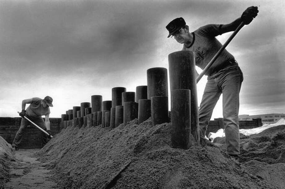 Mike Forbragd, left, and Mike Smith put wet sand around the bases of the tubes for a Seattle show on July 3, 1989. Photo: P-I File