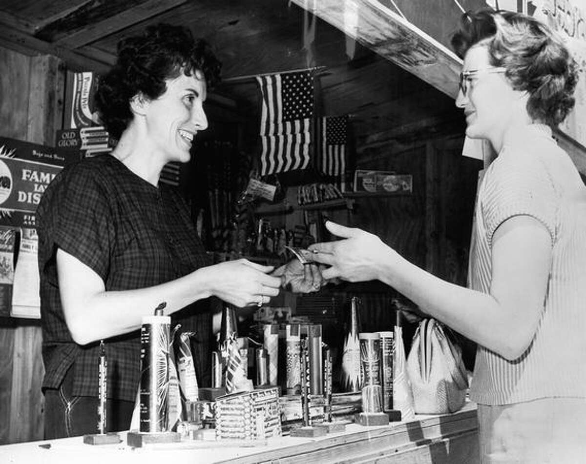 The original caption read: Mrs. Bernie Botz sells fireworks to a costumer on July 2, 1963.