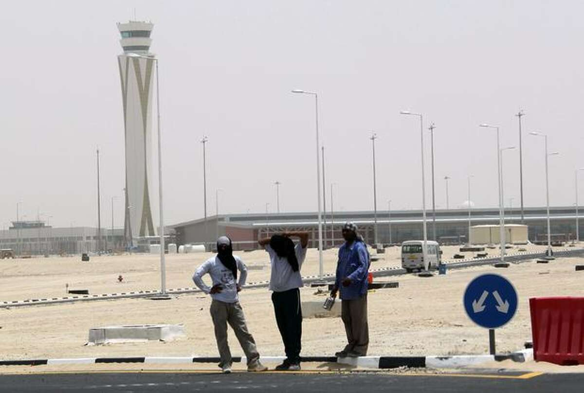 Asian Workers stand outside the new Dubai World Central-Al Maktoum International airport, on the outskirts of the Gulf emirate, as the first plane landed on the sole runway of the new airport, which is touted to become the world's largest when completed, with services initially confined to cargo traffic.