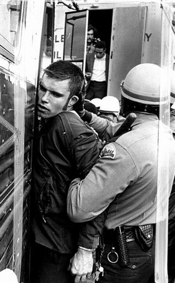The Nov. 6, 1969 photo caption read: An officer held a demonstrator against a bus after violence flared inside the Sea-Tac terminal. In background, a civil defense truck from King County, into which 20 arrested demonstrators were put and manacle-chained. (seattlepi.com file) Photo: P-I File