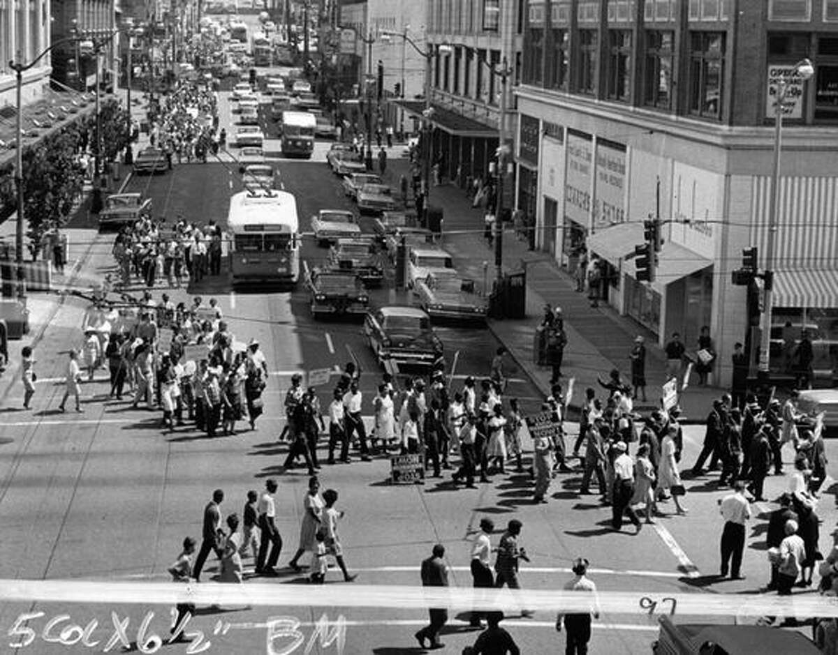 The original caption from June 15, 1963 said: Walking six abreast, Negro and white marchers carry placards decrying racial discrimination, turn the corner at Fifth Avenue and Pine Street in downtown Seattle. Their destination is Westlake Mall, scene of a large rally. More of the nearly 1,000 demonstrators in the distance are walking toward the intersection, west in Pine Street. (seattlepi.com file)
