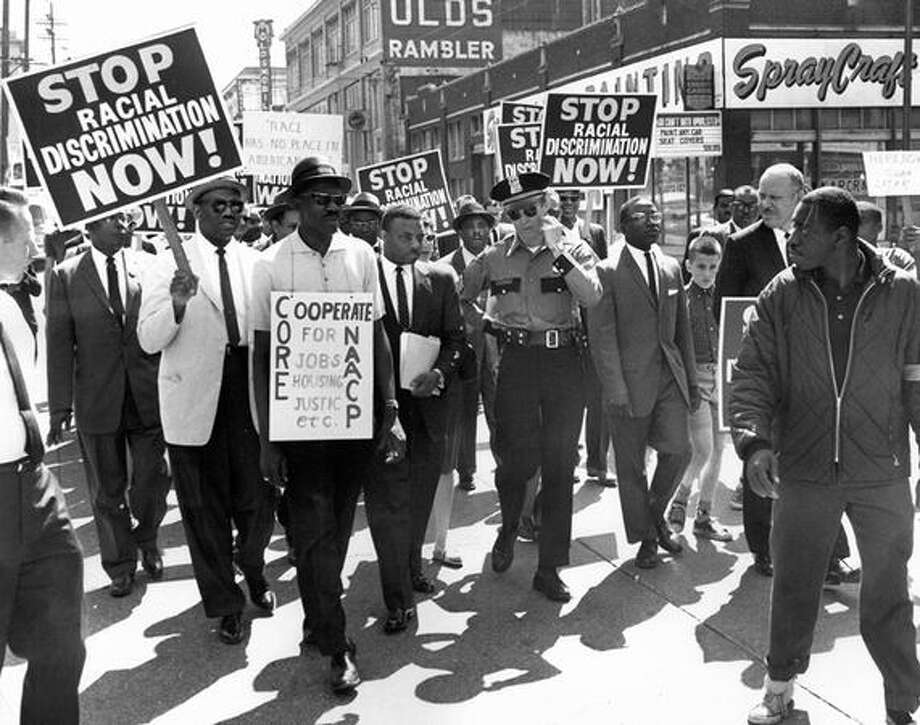 A Seattle march on June 15, 1963. The original caption read: Police Sgt. C.R. Connery chats with Rev. Mance Jackson urging marchers to tighten ranks to avoid traffic problems. (seattlepi.com file) Photo: P-I File