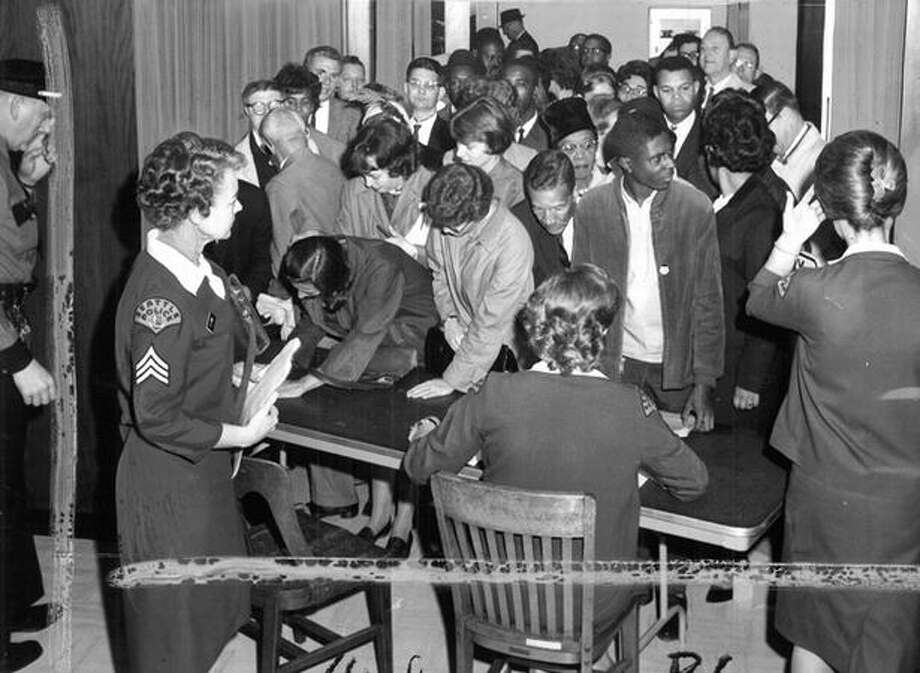 This undated photo shows visitors at Seattle City Hall for a housing ordinance. A policewoman supervises. (seattlepi.com file) Photo: P-I File