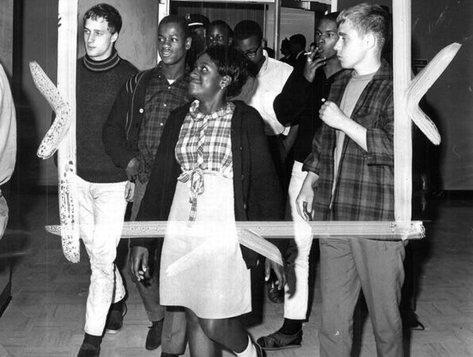 The Aug. 19, 1965 photo caption read: Members of the Central Area Youth Action Committee leaving the mayor's office (no names). This group declined to leave voluntarily; they insisted on being escorted. They were, by police. (Phil H. Webber/seattlepi.com file) Photo: P-I File
