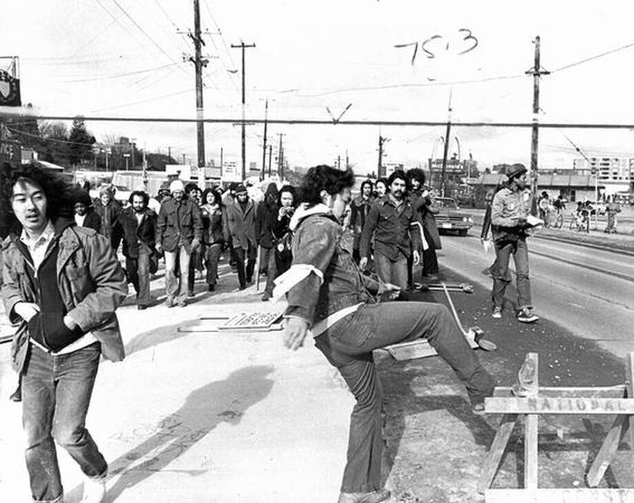 A demonstrator kicks over a street barricade during a protest demanding more minority workers be hired, Feb. 17, 1975. (Tom Brownell/seattlepi.com file) Photo: P-I File