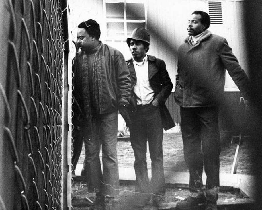 "The caption for this previously unpublished Dec. 1970 P-I photo read: Tyree Scott, head of the United Construction Workers Association, shown here at left, talks to newsmen in Seattle Thursday after about 50 UCWA members hurdled a construction fence and shut down a University of Washington construction project. Scott told newsmen, on other side of fence, ""hell no, we won't go"" until the groups demands for increased minority hiring of construction workers are met. [The other two men weren't identified.] (seattlepi.com file) Photo: P-I File"