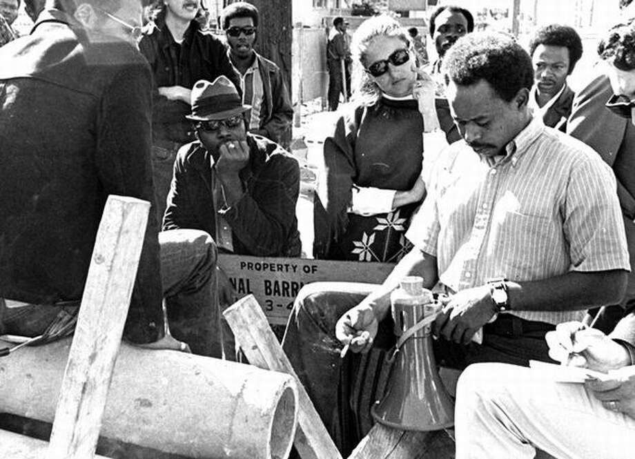 The caption for the Sept. 10, 1970 photo caption reads: Tyree Scott held a bullhorn and pondered a reporter's question. He led the march that closed down three construction projects. (Tom Brownell/seattlepi.com file) Photo: P-I File