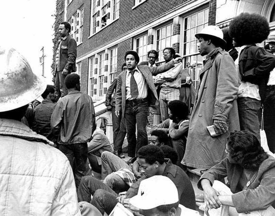 The photo caption for this previously unpublished June 7, 1972 P-I photo reads: Tyree Scott and Rep. Michael Ross speak to Garfield High School students this afternoonat approximately 2:30 p.m. Scott stands with his hands at his side. Ross is at the center and his left arm is pointing toward a Garfield doorway. (seattlepi.com file) Photo: P-I File
